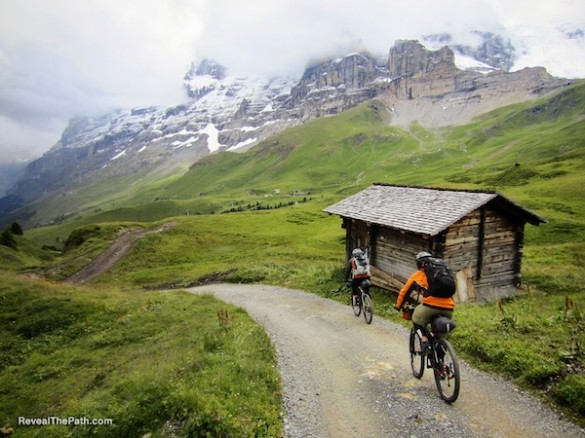 "Riders coast along a mountain road in the Swiss Alps while filming the documentary ""Reveal the Path."""