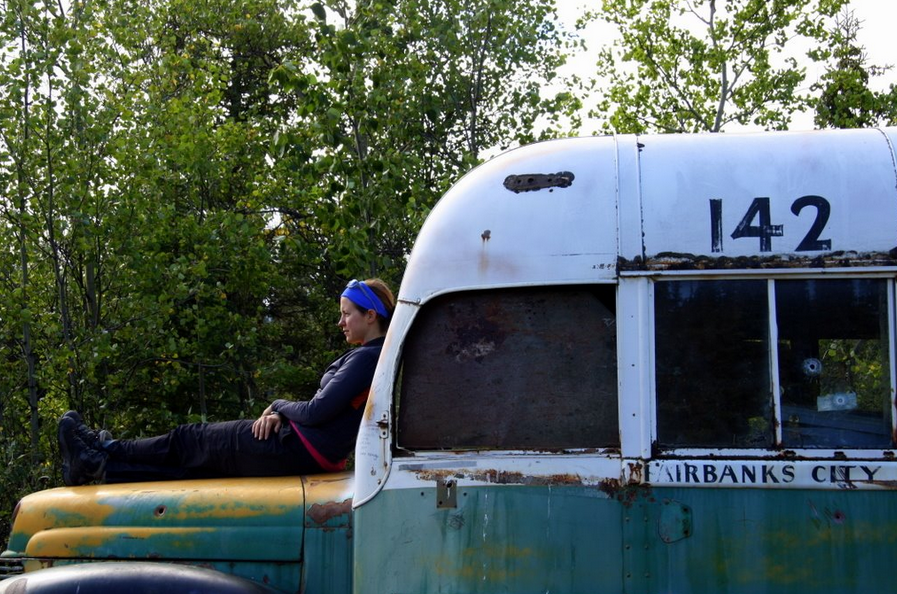 "Heather Horton rests on the hood of the ""Magic Bus"" once occupied by Christopher McCandless near Healy, Alaska. Photo by Ed Plumb"
